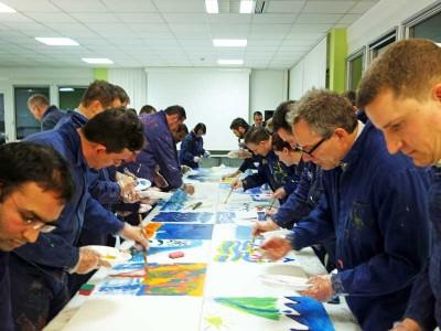 Ein Team malt gemeinsam Bilder zu einem Thema