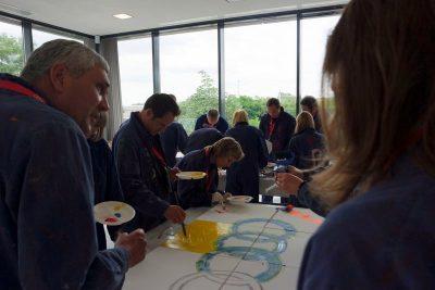 Visonsentwicklung mit einem Teambild am Mitarbeitertag, gemeinsam malen und kreativ sein