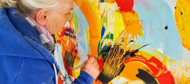 Künstlerin Etelka Kovacs-Koller malt Details eines Acrylbildes